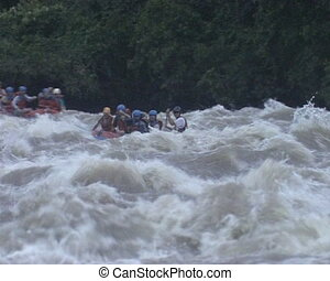 People in rubber boats sail down wildwater river. Extreme risky recreation.