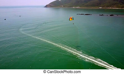 tourist sails with parachute over ocean - Drone shows...