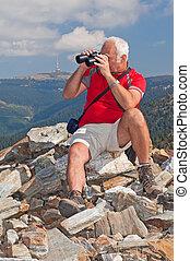 Tourist - Senior tourist on the top of mountain massif ...