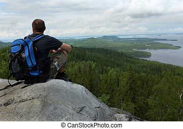 tourist sits on a cliff in the national park Koli, Finland