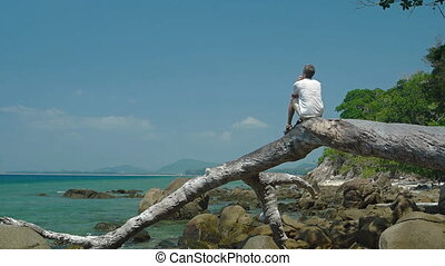 Tourist Sitting on Driftwood Log at Rocky Tropical Beach -...