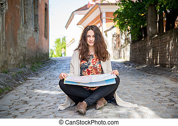 tourist smiling girl sitting on the ground