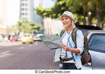 tourist standing on the sidewalk of an urban street