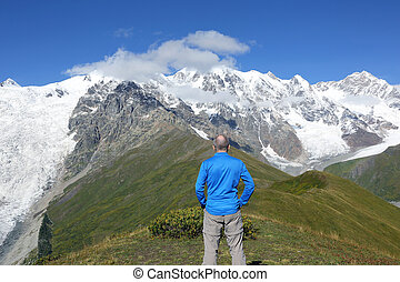 tourist stands on the background of a mountainous landscape