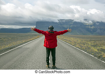 Tourist stands on the road against the mountain landscape in Iceland