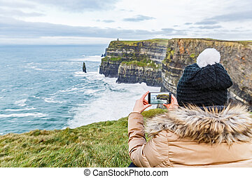 Cliffs of Moher - Tourist taking a photo with smartphone...