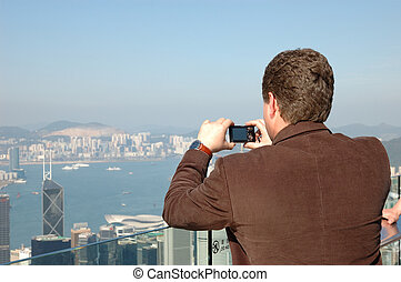 Tourist taking photo of Hong Kong skyline