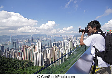 Tourist taking photo of Hong Kong skyline by his digital ...