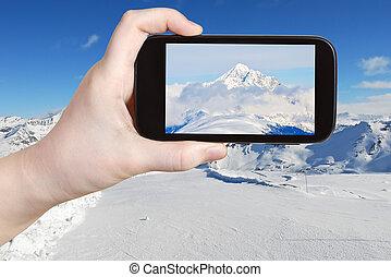 tourist taking photo of mountain peak in Alpes - travel...
