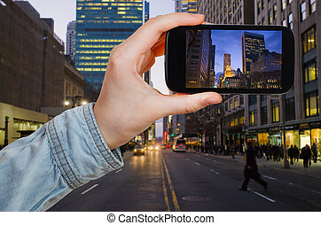 tourist taking photo of New York City in night