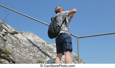 Tourist taking photo on his smartphone