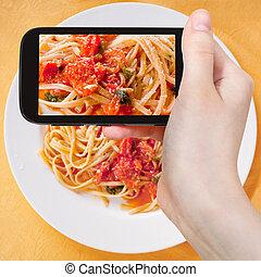 tourist taking photo spaghetti with tomato sauce