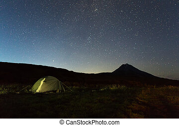 Tourist tent against night sky and Vilyuchinsky stratovolcano. Brookvalley Spokoyny at the foot of outer north-eastern slope of caldera volcano Gorely.