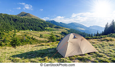 Tourist tent in mountains on a summer sunny day