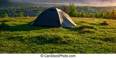 Tourist tent on green grass at sunrise.