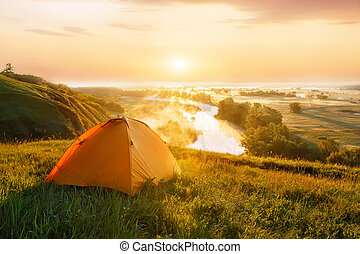 tourist tent on meadow at sunrise