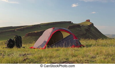 Tourist tent on meadow at the mountain in summer. - Tourist...