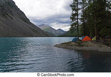 Tourist tents on the shore of a mountain lake. Altai, Russia.