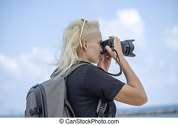 Tourist traveler photographer taking pictures of landscape on photo camera , hipster girl with backpack enjoying beautiful sea landscape. Close up portrait young tourist of a blonde girl
