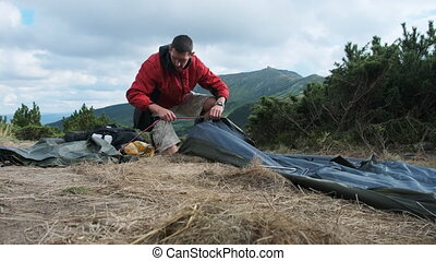 Tourist Traveler Sets Up a Single Tent in the Mountains. ...