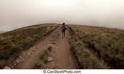 Tourist trekking mountains covered with clouds going to point of interest (pov)