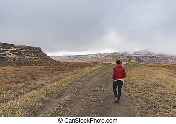 Tourist trekking on marked trail in the Golden Gate Highlands National Park, South Africa. Scenic table mountains, canyons and cliffs. Adventure and exploration in Africa.