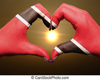 Tourist trinidad tobago made by america flag colored hands showing symbol of heart and love during sunrise