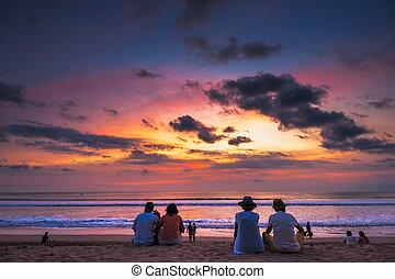 Tourist viewing sunset at Kuta Beach, Bali.