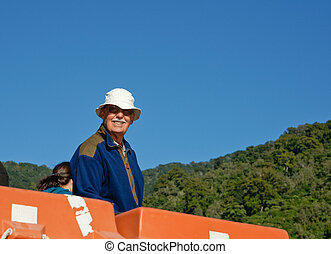Tourist standing at back of a boat viewing the scenery.
