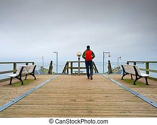 Tourist walk in autumn mist on wooden pier above sea. Rainy day
