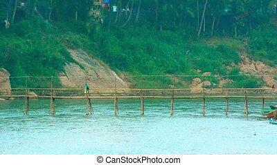 Tourist Walking across Bamboo Bridge in Laos - 1920x1080...