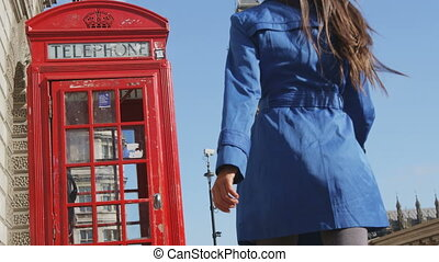 Woman walking by red telephone booth. Big Ben and Westminster Bridge are in the background. Casual professional or female tourist is wearing long blue trench coat by phone booth. RED EPIC SLOW MOTION.