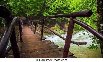 Tourist Walking On Bridge Hanging Above Rough River