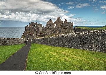 Tourist walking to main entrance of Dunluce castle