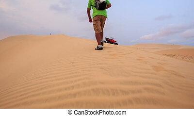 Tourist Walks along Crest in White Sand Dunes against...