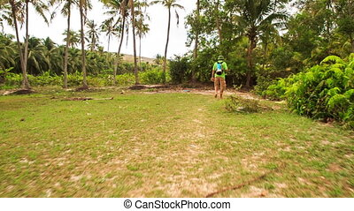 Tourist Walks on Hill Top Grass to Palms in Park