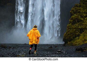 Tourist walks to the Skogafoss waterfall in Iceland