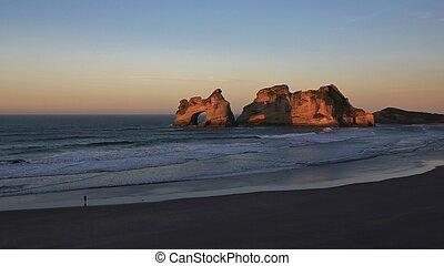 Tourist watching sunset at Wharariki Beach
