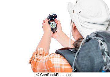Tourist with a backpack checks the direction of movement on the compass is isolated