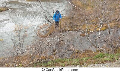 Tourist with a backpack goes through a mountain stream....