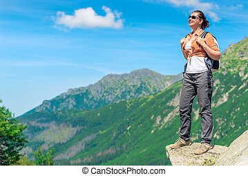tourist with a backpack in a mountain hike against the background of beautiful high mountains