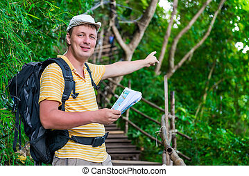 tourist with a backpack in the Asian jungle in the hike shows the direction of the route