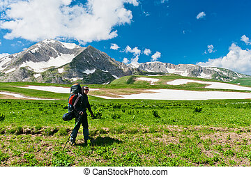 tourist with a backpack on the background of snowy mountains
