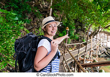 tourist with a backpack shows the direction of the route