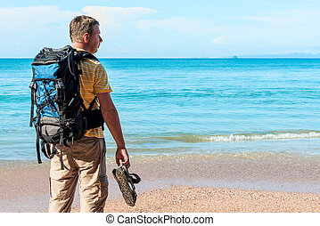 tourist with a backpack spends vacation on the beach, admires a beautiful view