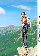 tourist with a backpack stretches his hand, shooting in the mountains