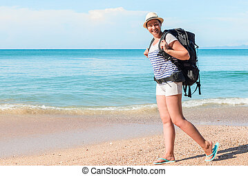 tourist with a backpack walks along the sandy beach of the resort of Thailand on a sunny day