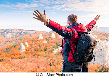 tourist with a backpack with open arms enjoying the autumn landscape in the mountains