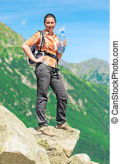 tourist with a backpack woman with a bottle of water high in the mountains relaxes