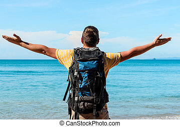 tourist with a big backpack on the beach with outstretched hands to the sides enjoy a beautiful view